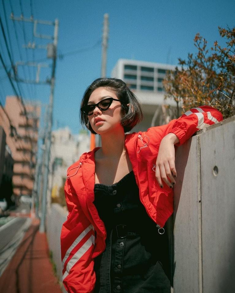 Mengenakan jaket merah dan kacamata hitam, Vanesha Prescilla tetap kece berpose di bawah sinar matahari.