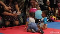 """Saat lomba merangkak, orang tua memberikan umpan dari HP, boneka, dompet, sampai foto si anak, agar anak bisa tiba di finis. (Foto: Yuni Ayu Amida)<div dir=""""auto"""" style=""""font-family: sans-serif; font-size: 12.8px;""""></div>"""