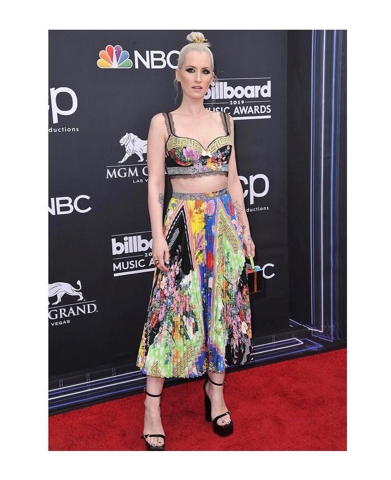 Inggrid Michaelson, menggunakan pakaian dengan corak bertumpuk model rok lipit.