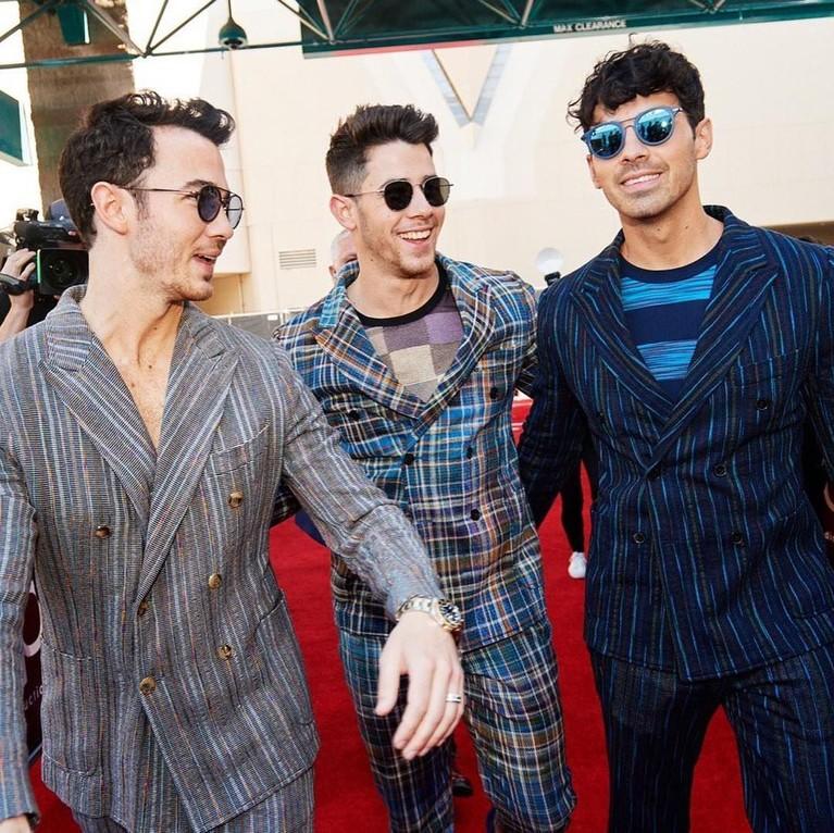 The Jonas Brothers.(Kiri ke Kanan, Joe, Nick dan Kevin) Berselisih satu sama lain dalam setelan denganmotif yang berbeda saat berpose bersama.