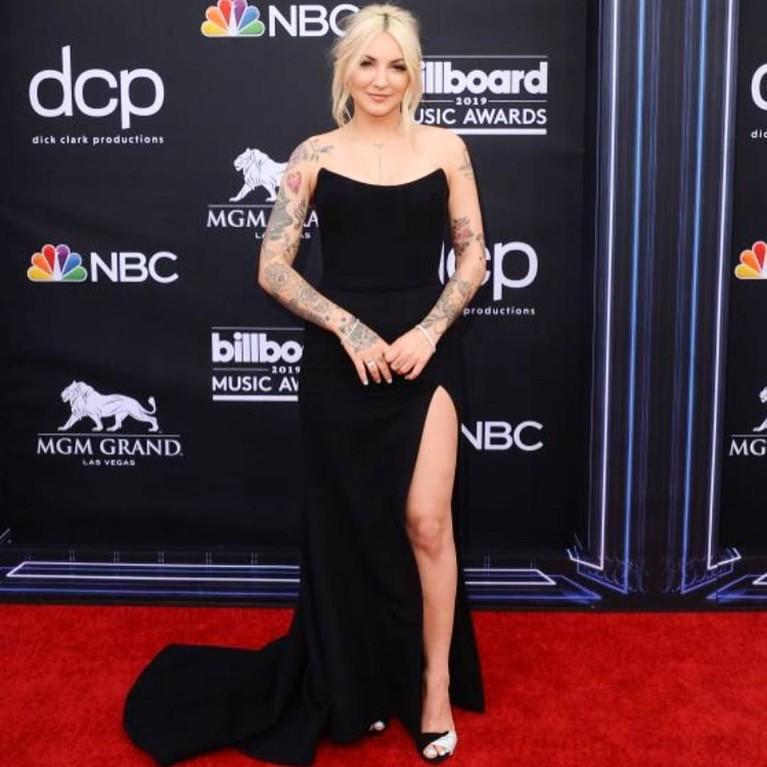 Julia Michaels, terlihat cantik dengan gaun berwarna hitam dengan belahan tinggi pada bagian kaki kirinya yang membuat kakinya terlihat jenjang dengan tatanan rambut pirangnya yang dibuat messy bun.