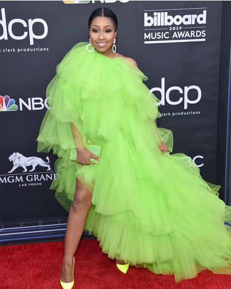 Yung Miami. Seorang penyanyi dari grup City Girls, mengenakan gaun gaun hijau limau besar, yang dilengkapi dengan sepatu kuning neon.