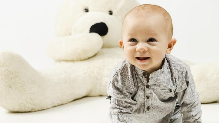 11 months old smiling baby boy in gray clothes is crawling on the white floor against huge teddy bear, studio shot.