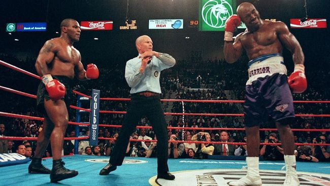 Referee Lane Mills (C) stops the fight in the third round as Evander Holyfield (R) holds his ear as Mike Tyson (L) watches 28 June 1997 during their WBA heavyweight championship fight at the MGM Grand Garden Arena in Las Vegas, NV. Holyfield won by disqualification in the the third round after Tyson bit his ear.   AFP PHOTO/JEFF HAYNES (Photo by JEFF HAYNES / AFP)