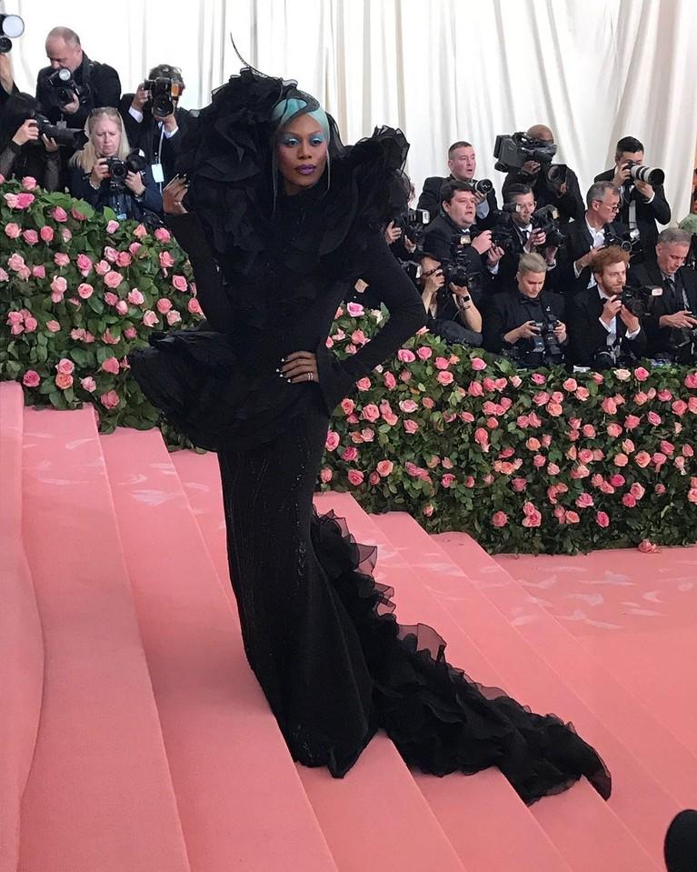 Laverne Cox,mengenakan gaun hitam yang mewah lengkap dengan aksesoris kepalanya hasil karya Christian Siriano Black.