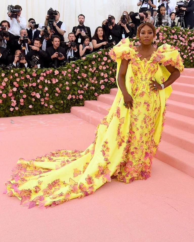 Atlit Tenis, Serena Williamsmengenakan gaun berwarna neon kuning dengan bahu yang besar dan detail berwarna pink. Gaun yang ia kenakan ini hasil karya dari desainer terkenal Versace.