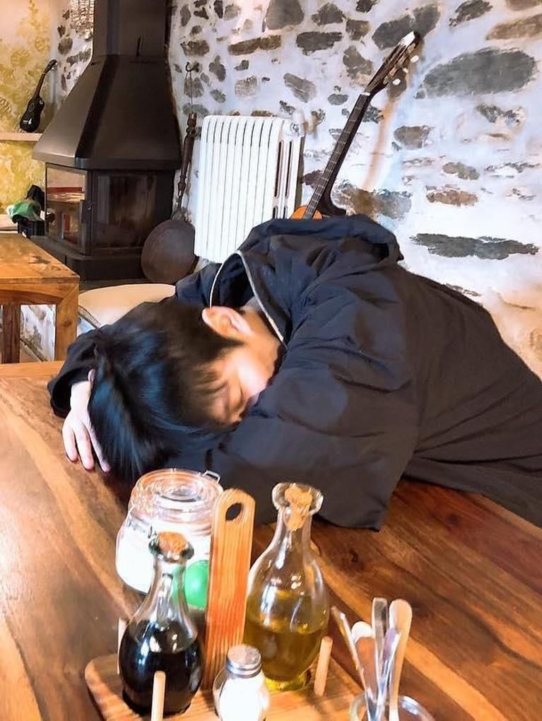 Potret Lee Min Ho kelelahan setelah menjalani aktivitas. Ia tampak tertidur di atas meja dengan berbantal tangan.