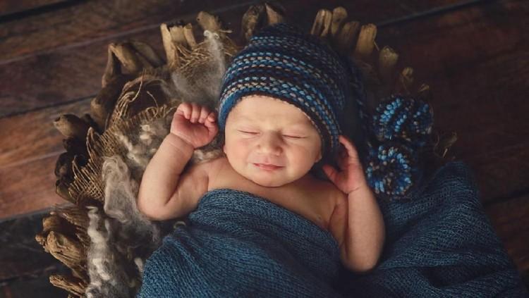 A newborn baby smiles in his sleep. He is ten days old.