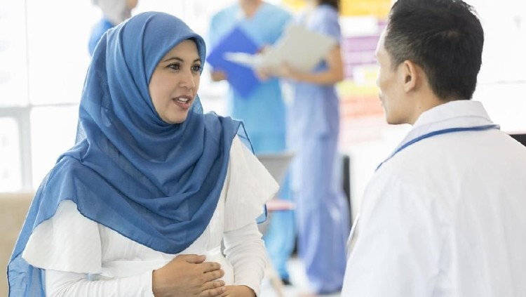 Maternity patient talks with ob/gyn holds her abdomen while discussing something with doctor during prenatal appointment.