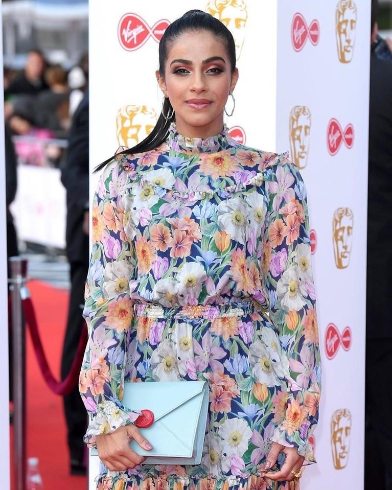 Mandip Gill, terlihat aneh dengan gaun kerah tinggi bernuansa bunga-bunga dengan sepasang sepatu yang berbeda warna.