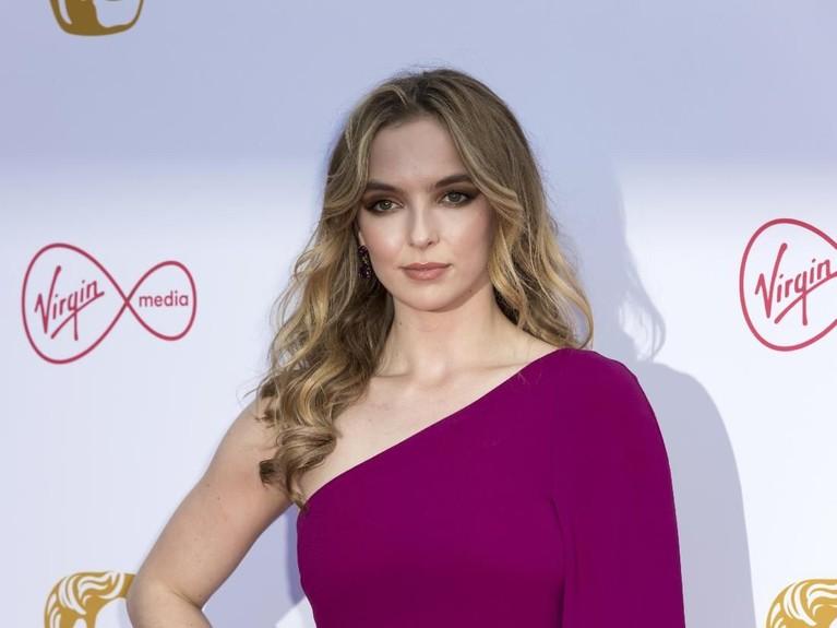 Jodie Comer. Pemain Killing Eve ini tiba di pergelaran karpet merah mengenakan gaun off shoulder rancangan Stella McCartney dengan warna burgundy.