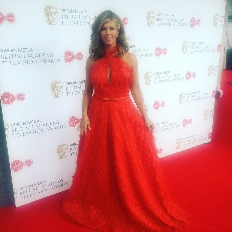 Presenter Kate Garrawaymengenakan gaun bulu berwarna merah terang.