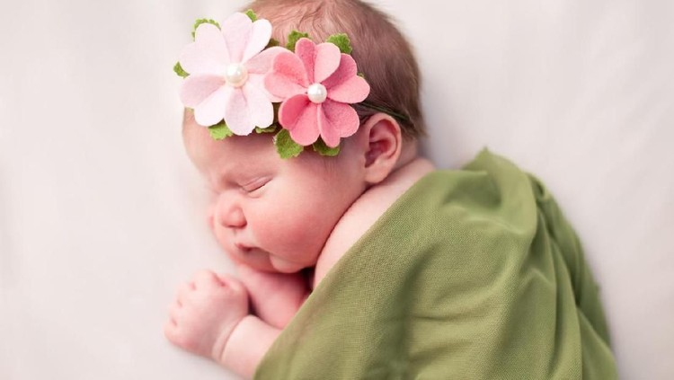 Color image of a newborn baby girl wearing flowered headband and sleeping peacefully while swaddled in a soft, green blanket. Image is on white background.