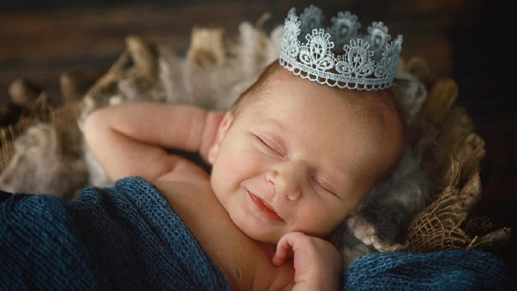 A newborn baby boy smiles as he wears a silver crown. A prince is born!