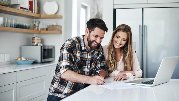 Shot of a young couple using a laptop and going through paperwork at home