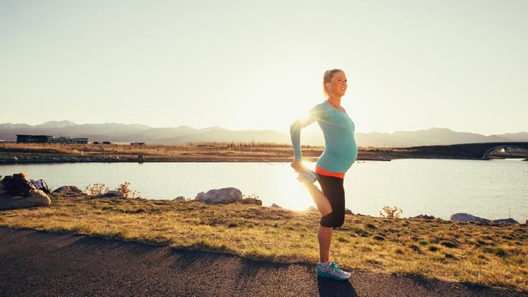 A pregnant female runner in a blue athletic shirt and running shoes is training while pregnant for her next race. She warms up by stretching with the sun flaring behind her. This woman enjoys running on trails and at sunset in the evening. Running is her favorite exercise to stay fit and happy.