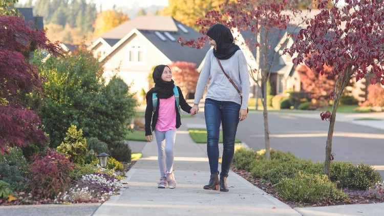 A mother wearing a traditional headscarf picks up and hugs her elementary age daughter, who is also wearing a headscarf,  before she heads off to school. They're on a sidewalk in a suburban neighborhood.