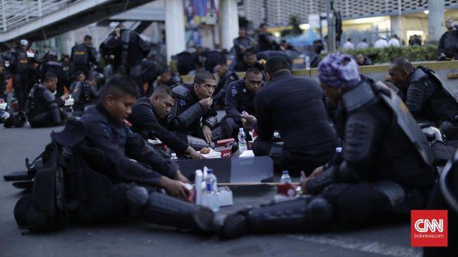 Polisi yang bertugas menghadapi massa perusuh tetap melaksanakan ibadah puasa dan rela bersantap sahur di tengah jalan demi keamanan.