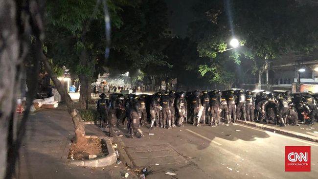 Tameng polisi anti huru-hara sempat terbakar karena api dari molotov yang dilempar pengunjuk rasa di Jalan KH Wahid Hasyim.