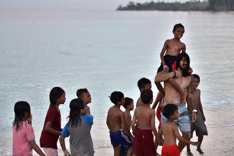 Jermiah dan Inka juga akan menikmati suasana Pantai Jikumerasa, Maluku, yang teduh sambil bermain dengan anak-anak, penduduk lokal.