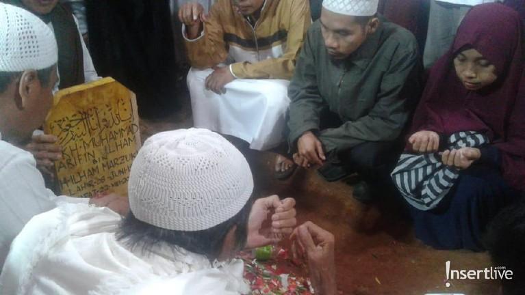 Dua putra ustaz Arifin Ilham, Alvin dan Ameer turun ke liang lahat. Mereka mengantarkan sang ayah ke tempat peristirahatan terakhirnya. Usai dimakamkan, jemaah langsung berdoa di depan makam.