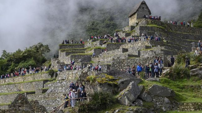 Tourists visit the Machu Picchu complex, the Inca fortress enclaved in the south eastern Andes of Peru on April 24, 2019. (Photo by Pablo PORCIUNCULA BRUNE / AFP)