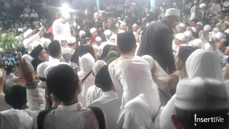 Ketika jenazah Ustaz Arifin Ilham tiba di pemakaman, semua jemaah berebut ingin mengangkat keranda almarhum. Lantunan zikir dan doa terus berkumandang di pemakaman Arifin Ilham.