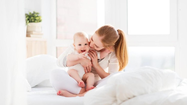happy family mother playing and hug with newborn baby  in bed