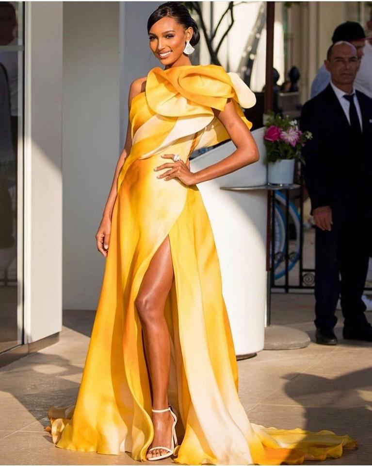 Jasmine Tookes,mengenakan gaun panjang perpaduan warna kuning cerah dan emas. Gaun ini memiliki belahan panjang di bagian kaki kirinya. Jasmine tampak cantik dan bersinar dengan gaun mewahnya tersebut.