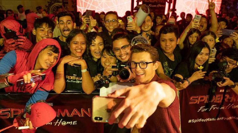 Tom juga mengambil telepon genggam milik penggemarnya dan lakukan swafoto bersama.