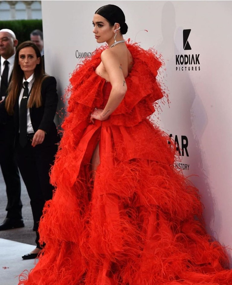 Dua Lipa,mengenakan gaun one shoulderberwarna merah menyala dengan model renda bertumpuk.