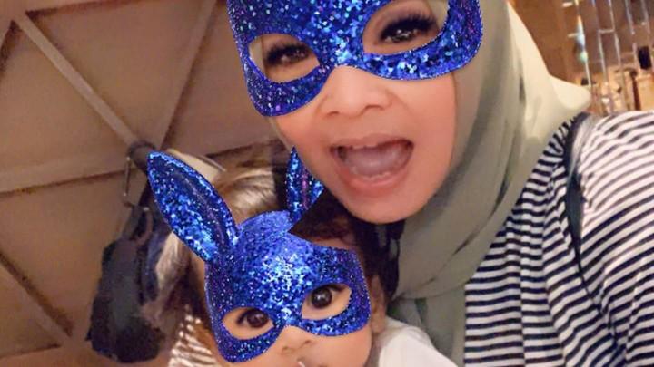 <p>Sekarang pakai <em>filter</em> topeng berwarna biru berkilauan. Wah ekspresi Ansara enggak mau kalah seru dengan sang nenek. (Foto: Instagram: @rieta_amilia)</p>