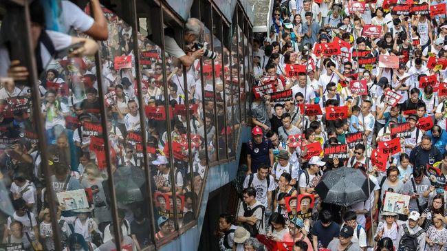Massa pro-demokrasi Hong Kong mengabaikan larangan polisi dan nekat turun ke jalan untuk melakukan pawai menentang pemerintah, Minggu (20/10).