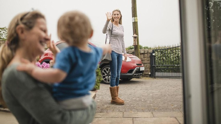 A women waves goodbye to her mother and son from across the street as she leaves the house.
