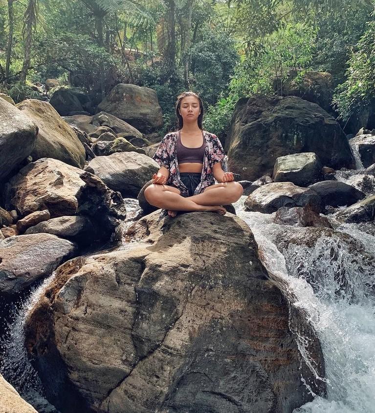 Angela yang hobi traveling sering membagikan momen jelajahnya di Instagram. Gaya busananya selama jalan-jalan itu pun selalu simpel seperti bikini dan cardigan yang ia pakai saat menikmati suasana tenang di bebatuan ini.