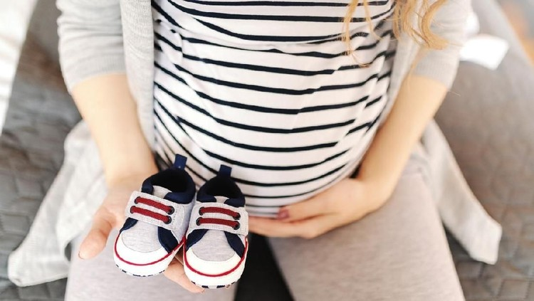 Close up of pregnant Caucasian woman holding baby shoes and touching belly.