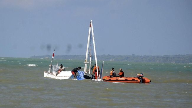 Petugas mengevakuasi perahu karam di Pantai Desa Romben Barat, Dungkek, Sumenep, Jawa Timur, Selasa (18/6/2019). Perahu berpenumpang sekitar 57 orang yang berlayar dari Pulau Raas menuju Kalianget itu, karam di perairan Pulau Sapudi-Pulau Giliyang, Sumenep, Senin (17/6). Dari jumlah penumpang tersebut  17 diantaranya meninggal dunia dan satu belum diketemukan. ANTARA FOTO/Saiful Bahri/pd.