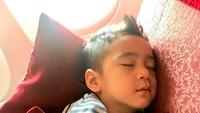 <p>Rafathar lucu juga ya, Bun, kalau sedang tidur begini? Di pesawat pun bisa nyenyak banget tidurnya. Aa lagi ikut Mama Gigi sama Papa Raffi nih ke Singapura. (Foto: Instagram @raffinagita1717)</p>