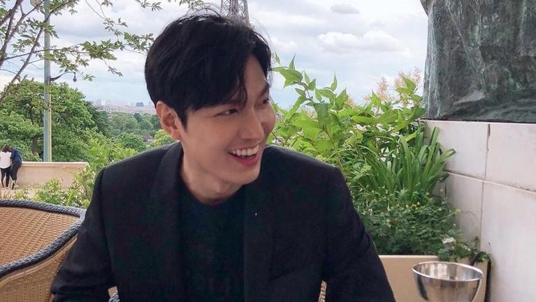 Mengenakan setelan formal serba hitam, Lee Min Ho terlihat tengah menikmati udara Paris di bagian luar ruangan sebuah kafe.