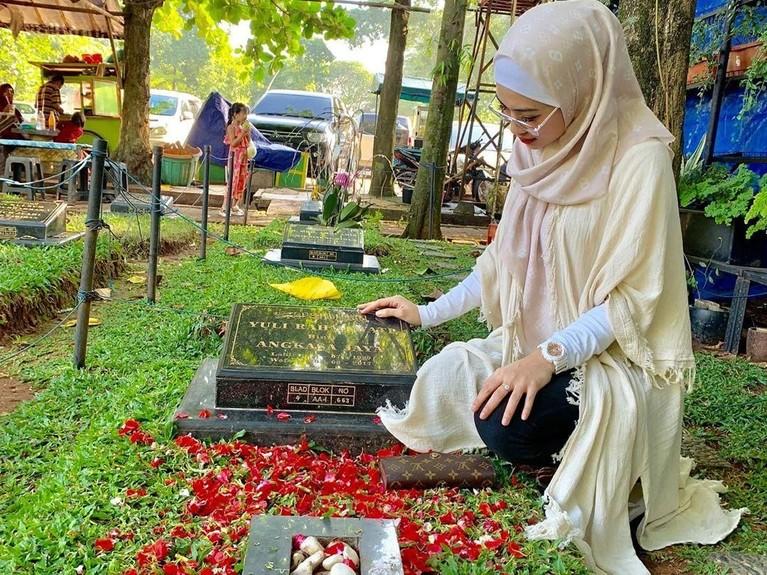 Della Perez tampak anggun berbusana gamis saat sedang mendatangi makam sang kakak, Julia Perez.