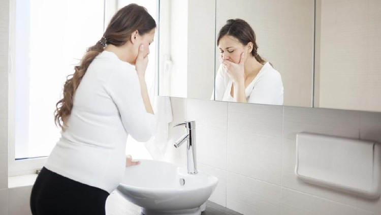 Young Pregnant Woman Suffering With Morning Sickness In Bathroom