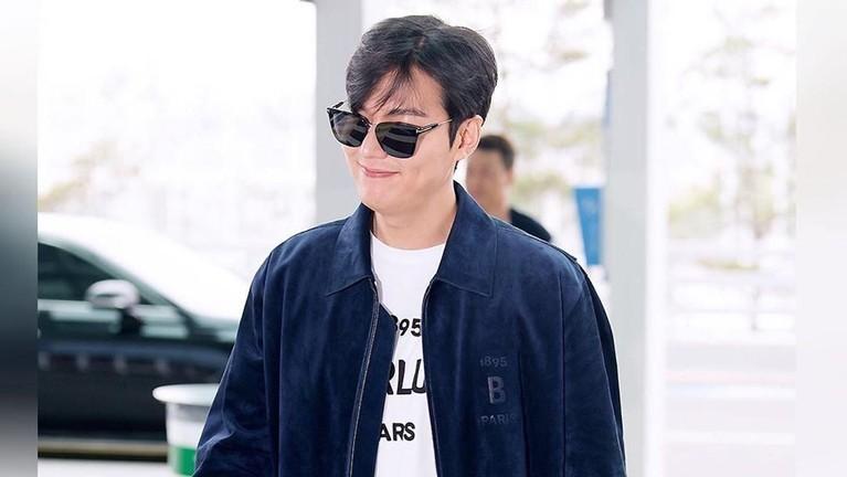 Gaya busana Lee Min Ho saat tiba di bandara terlihat begitu stylish, mengenakan kacamata hitam, kaus putih, dan jaket denim gelap.