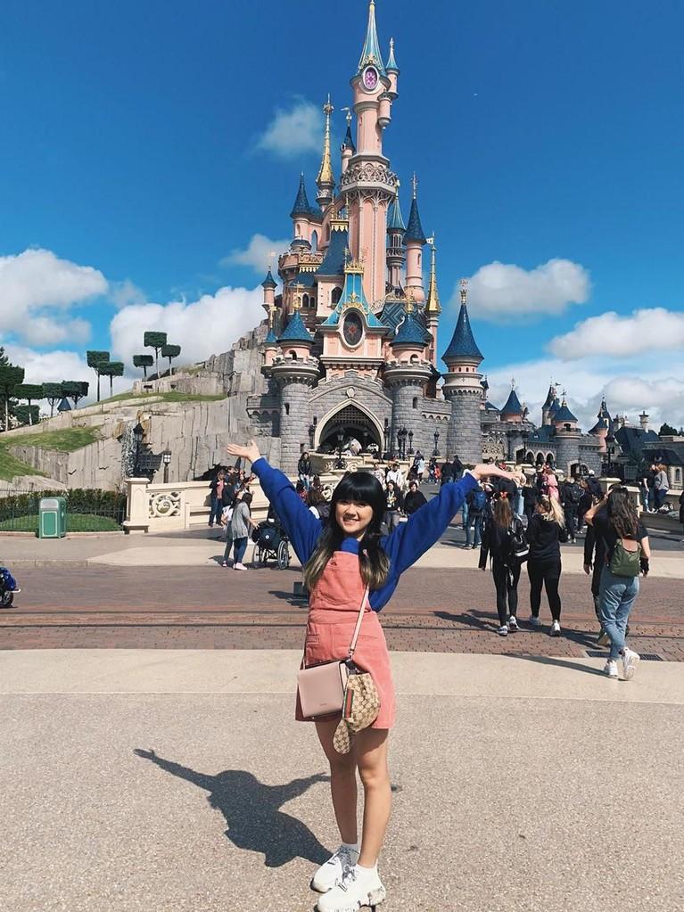 Cerianya Cigul yang menyempatkan waktunya untuk datang ke Disneyland, Paris. Cigul mengenakan overall merah muda yang dipadukan dengan kaus biru elektriknya.