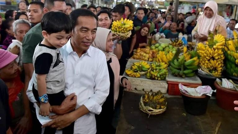 Jokowi yang menggendong Ethes saat singgah di Pasar Gede Solo. Jokowi beserta keluarga juga membeli beberapa peralatan dapur hingga makanan.