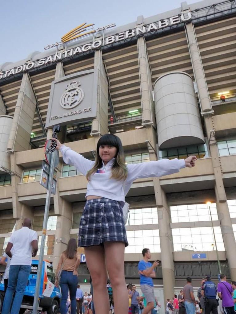 Perempuan yang akrab disapa Cigul itu berposen di depan stadion Estadio Santiago Bernabeu, Spanyol, untuk menunggu aksi dari tim sepak bola kesukaannya, Real Madrid.