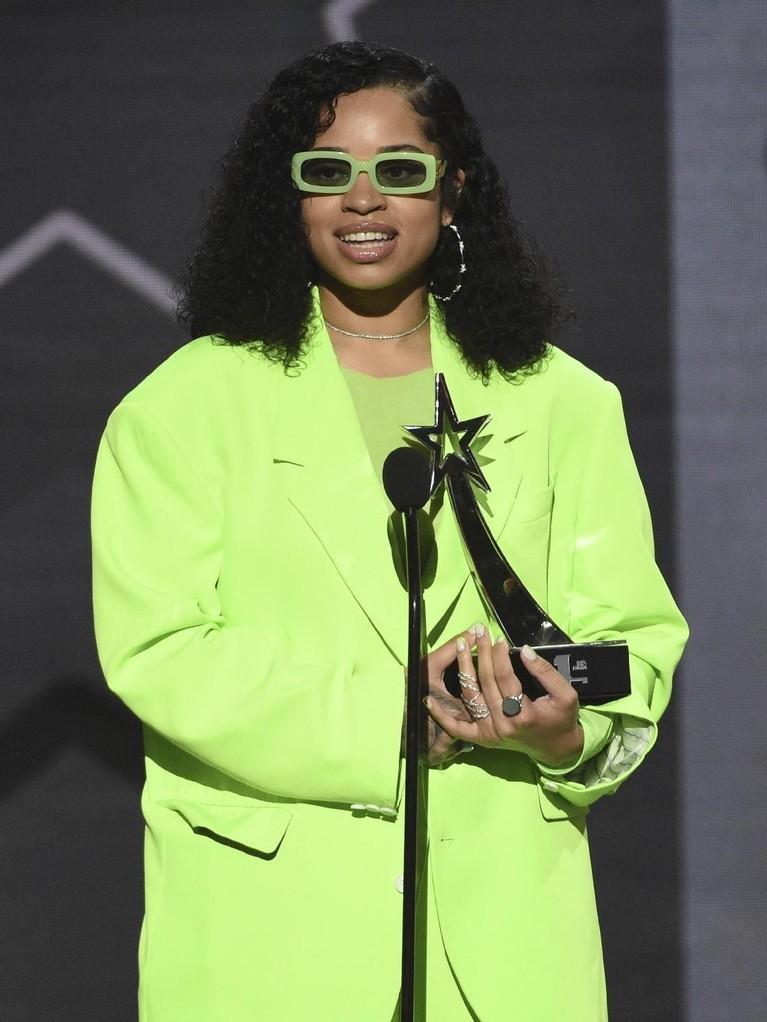 Ella Mai. Penyanyi sekaligus penulis lagu ini tampil dengan setelan pakaian warna neon. Bahkan netizen membandingkannya dengan salah satu karakter animasi di tahun 90an.