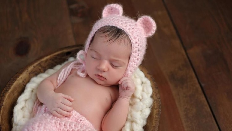 An overhead shot of a two week old newborn baby girl sleeping in a little, wooden bowl. She is wearing a crocheted, pink bear bonnet. Shot in the studio on a wood background.