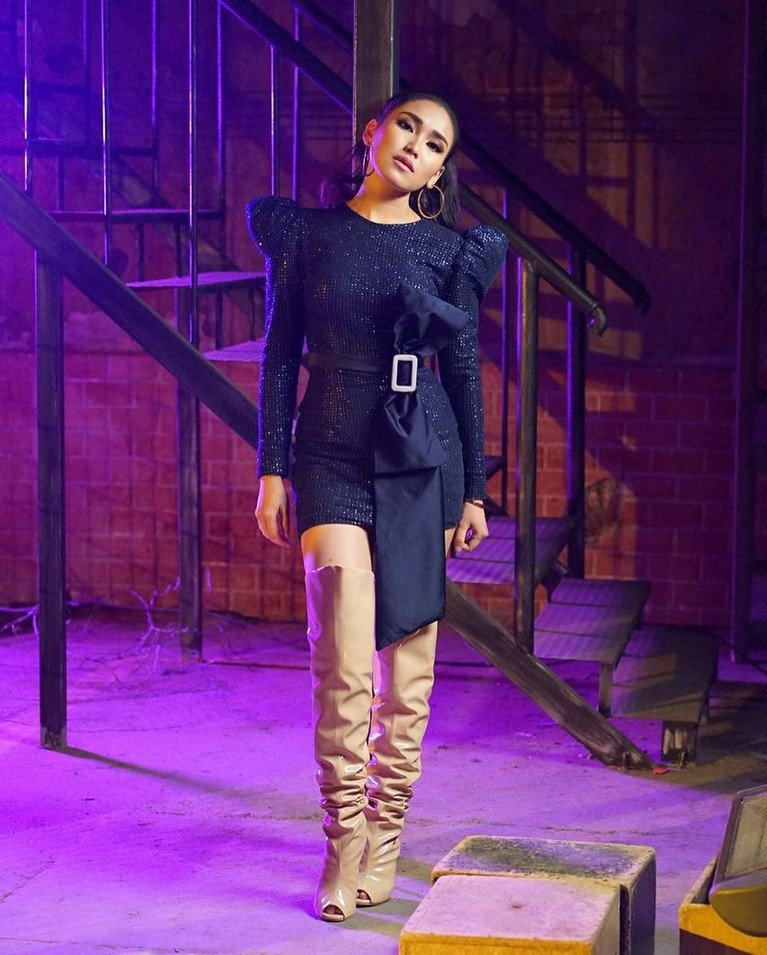 Tak hanya bisa tampil anggun dengan gaun panjang,Pelantun Sambalado inijuga tampil enerjik dengan mini dress asimetris yang dipadukan dengan high boots.