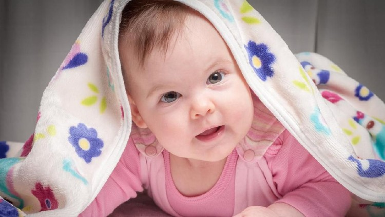 Smiling baby after shower with towel on head