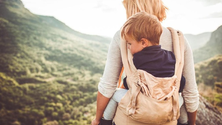 Photo of young woman and her toddler child, went to the top of the mountain by hiking in the nature. The boy is in a baby carrier, held by his mother.